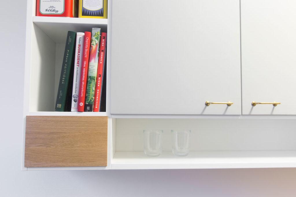 lähikuva 60-luvun tyylisestä keittiönkaapista ja avohyllyistä, joissa kirjoja ja peltipurkkeja