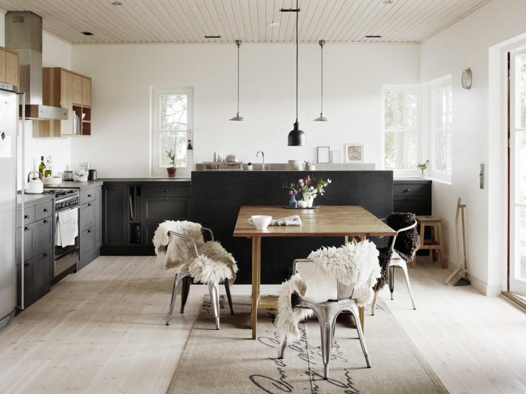 Upea umpipuinen keittiö, kaappien väreinä musta ja puu. Lattia ja seinät vaaleat