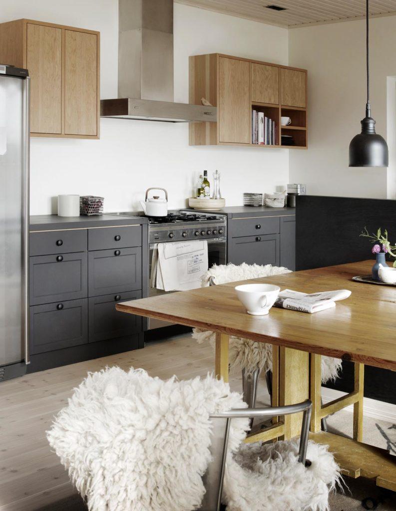 Moderni, mustan ja puun värinen keittiö ja keittiönpöytä, jossa metallisten tuolien päällä lampaantaljat