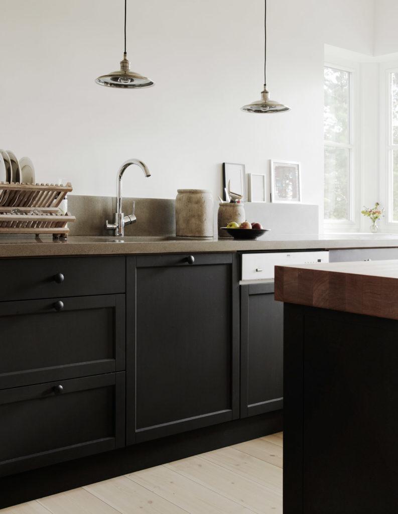 Mustat keittiön kaapit ja valkoinen seinä