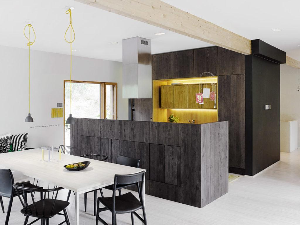 mustaksi petsattu puinen keittiö, jossa kellertävän vaalea syvennys.