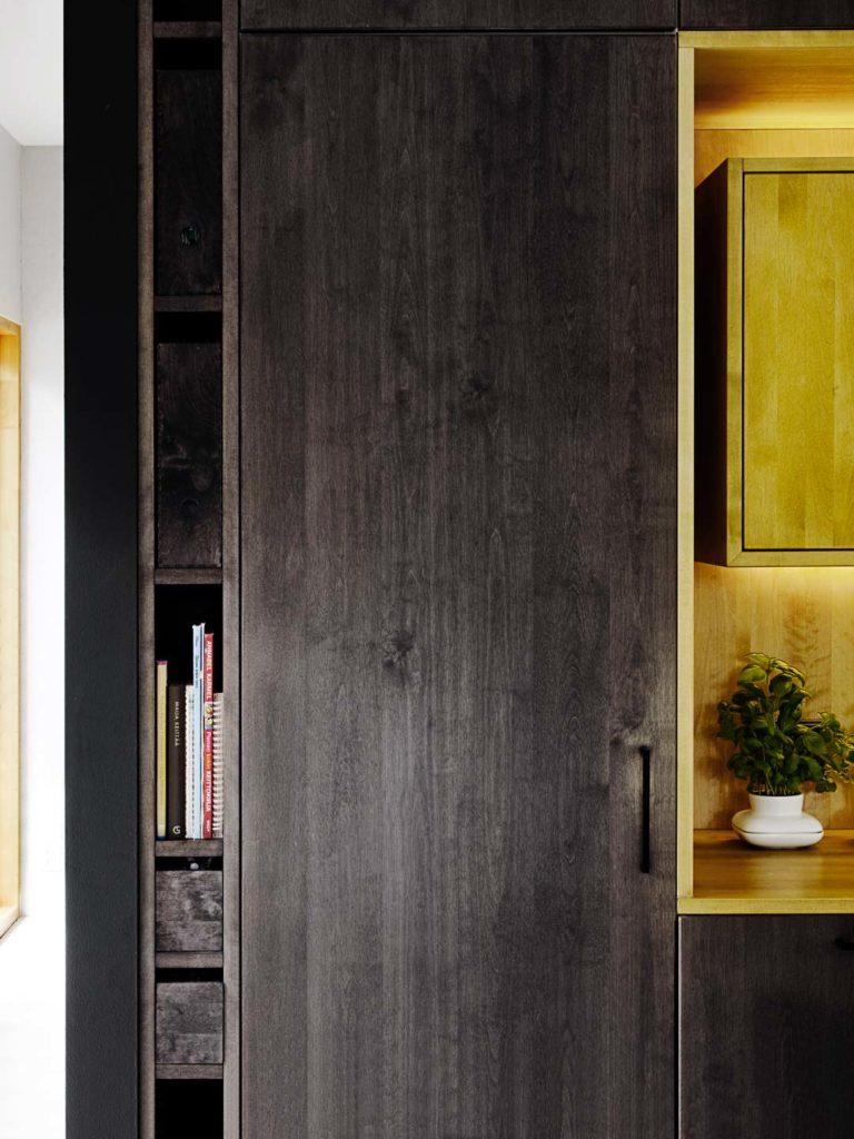 yksityiskohta mustasta keittiöstä jossa kellertävä puinen syvennys