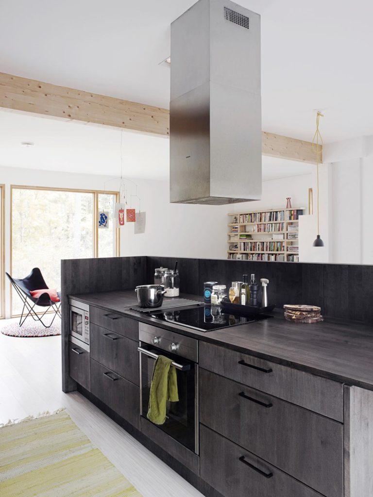 musta keittiösaareke vaaleassa asunnossa