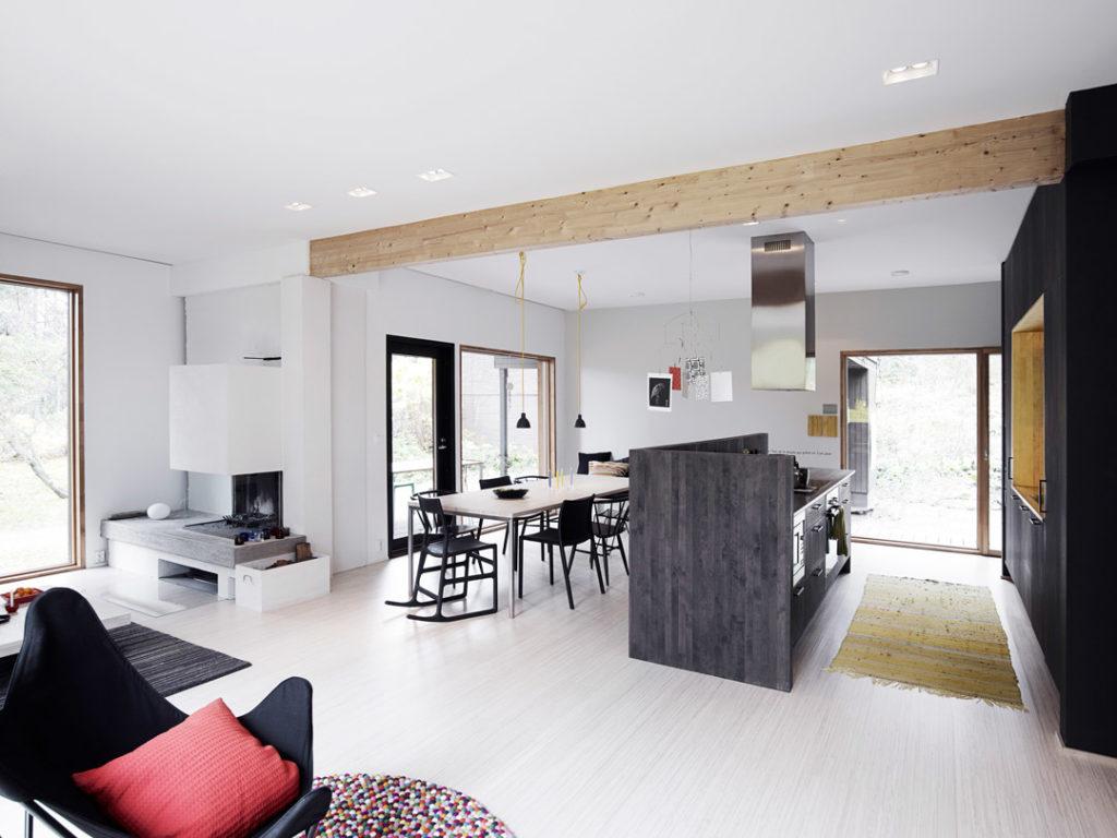 musta keittiö kuvattuna olohuoneesta päin, lattia ja seinät vaaleat, ruokaryhmä vaalea mustin tuolein