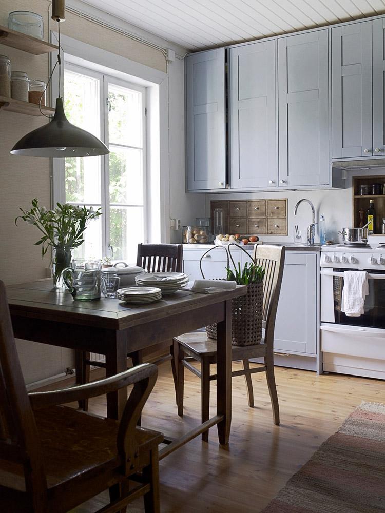 perinteinen kaunis keittiö, jossa siniharmaat kaapit ja seinään upotetut ruskeat laatikot