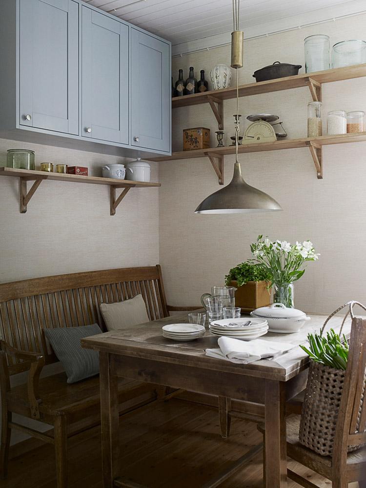 aamiaisnurkkaus. Vanhan pöydän ympärillä puinen sohvapenkki, pöydällä freesioita lasisessa maljakossa sekä astioita. Seinillä puisia hyllyjä, joissa vanhoja esineitä